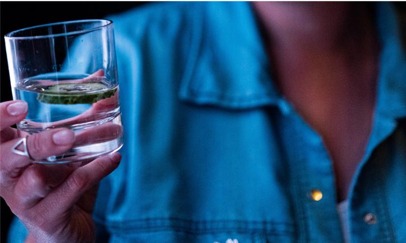 グラスに入った水を持つ手の画像